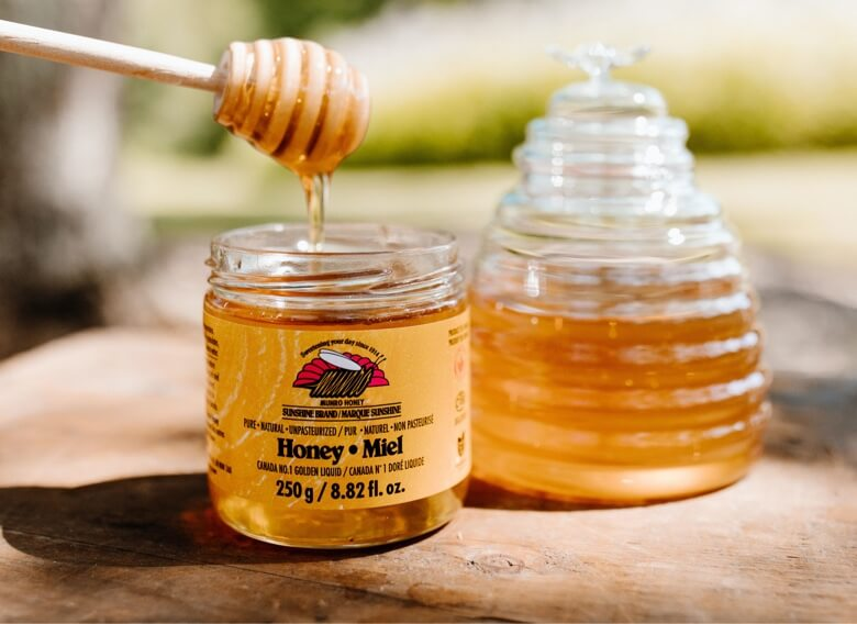 Munro Honey branded honey pot with honey dripping from wooden honey dripper